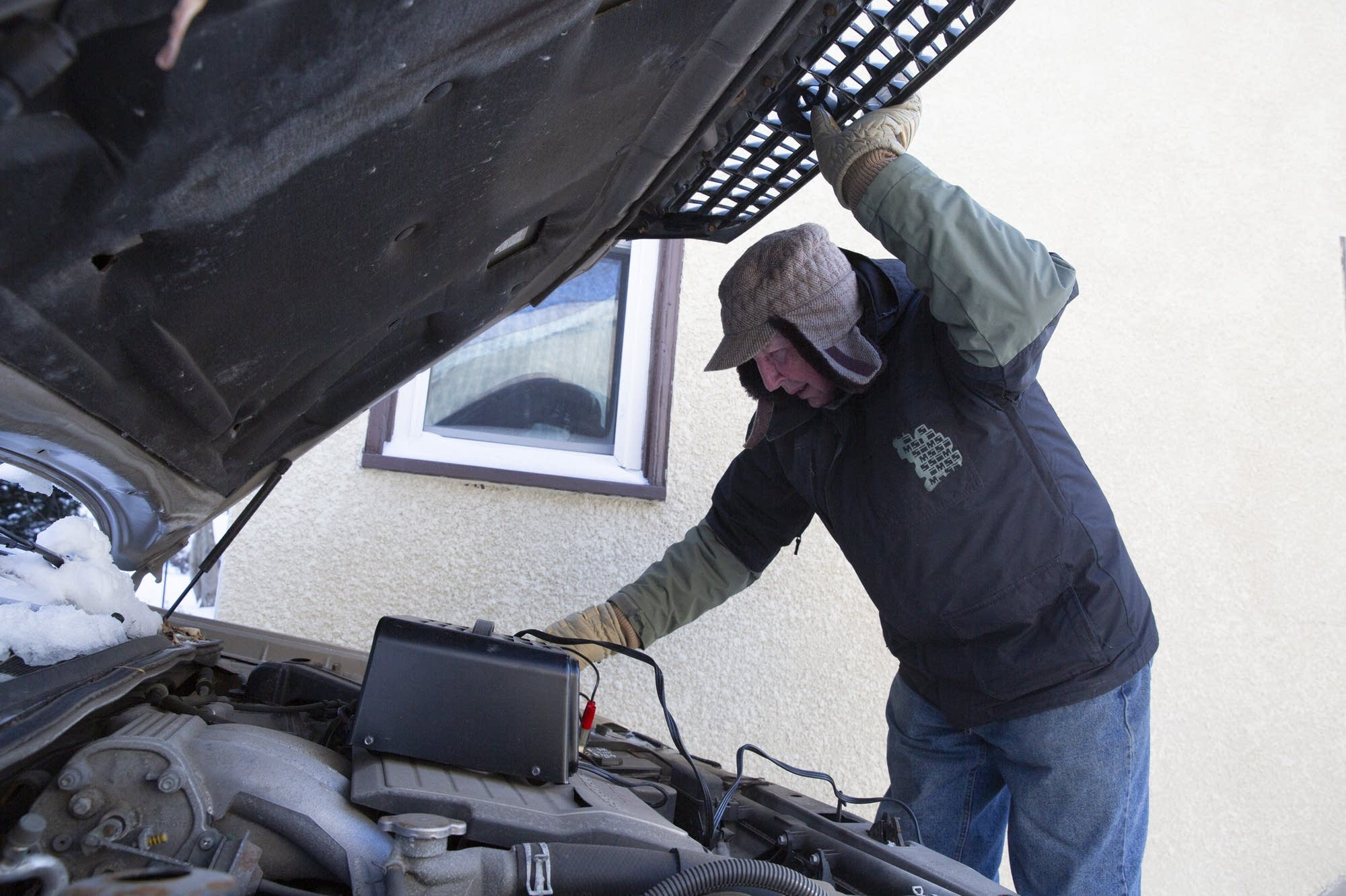 Leonard Elits of St. Paul uses a charger to jump start his car.