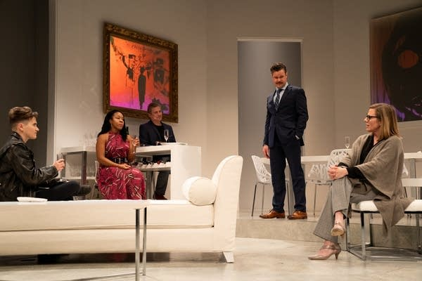 Five actors rehearse on a white stage.
