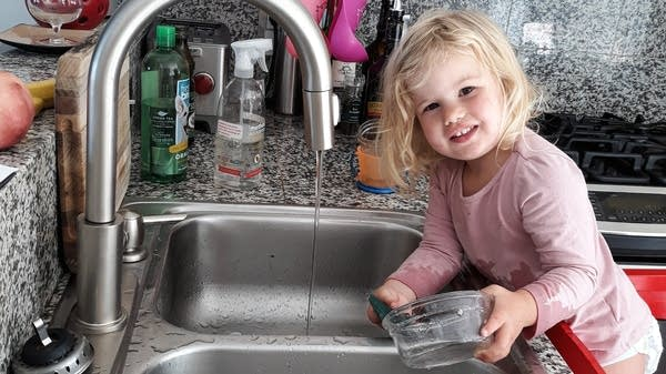 A kid helps her parent doing dishes.