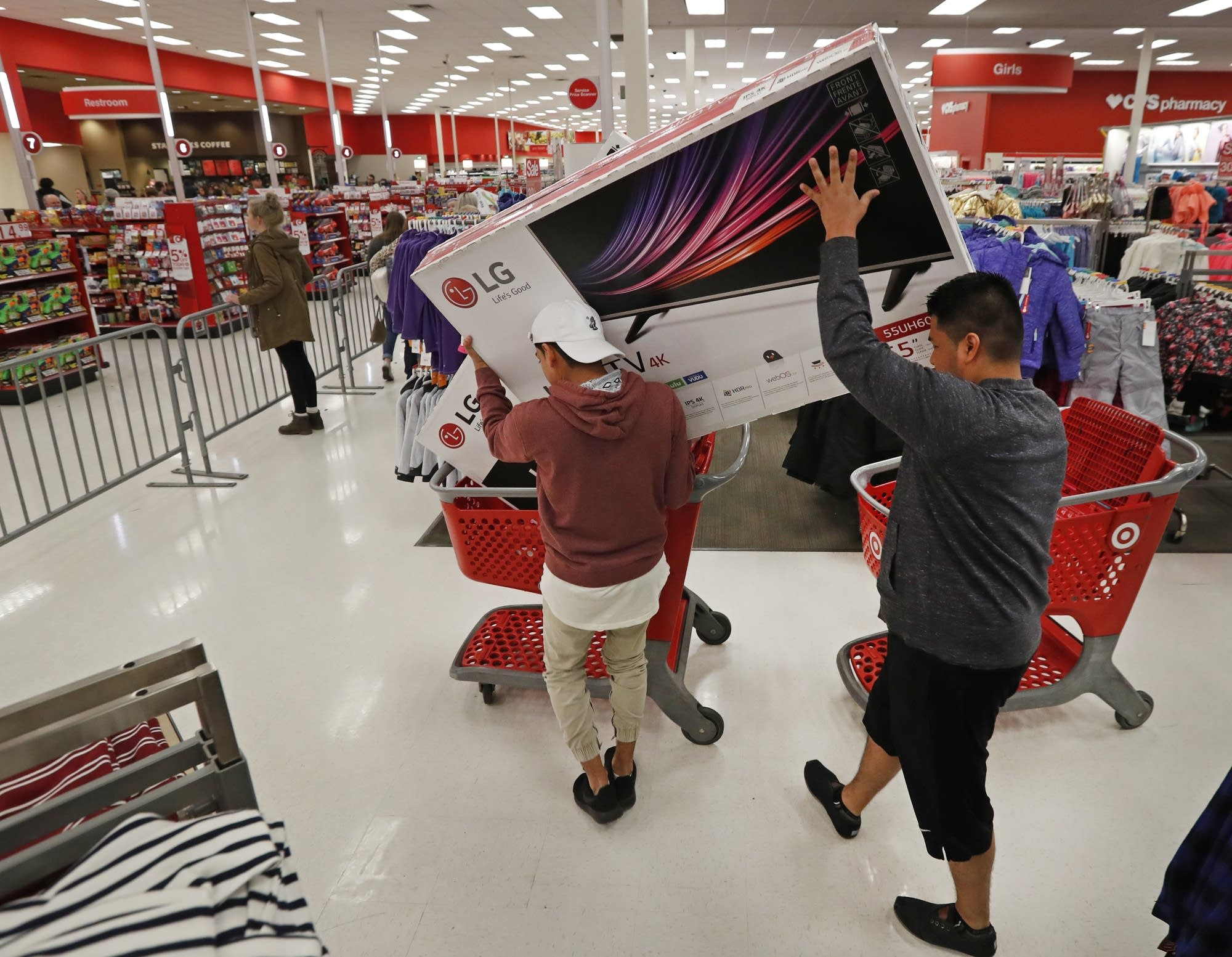 Shoppers put a TV in a cart.