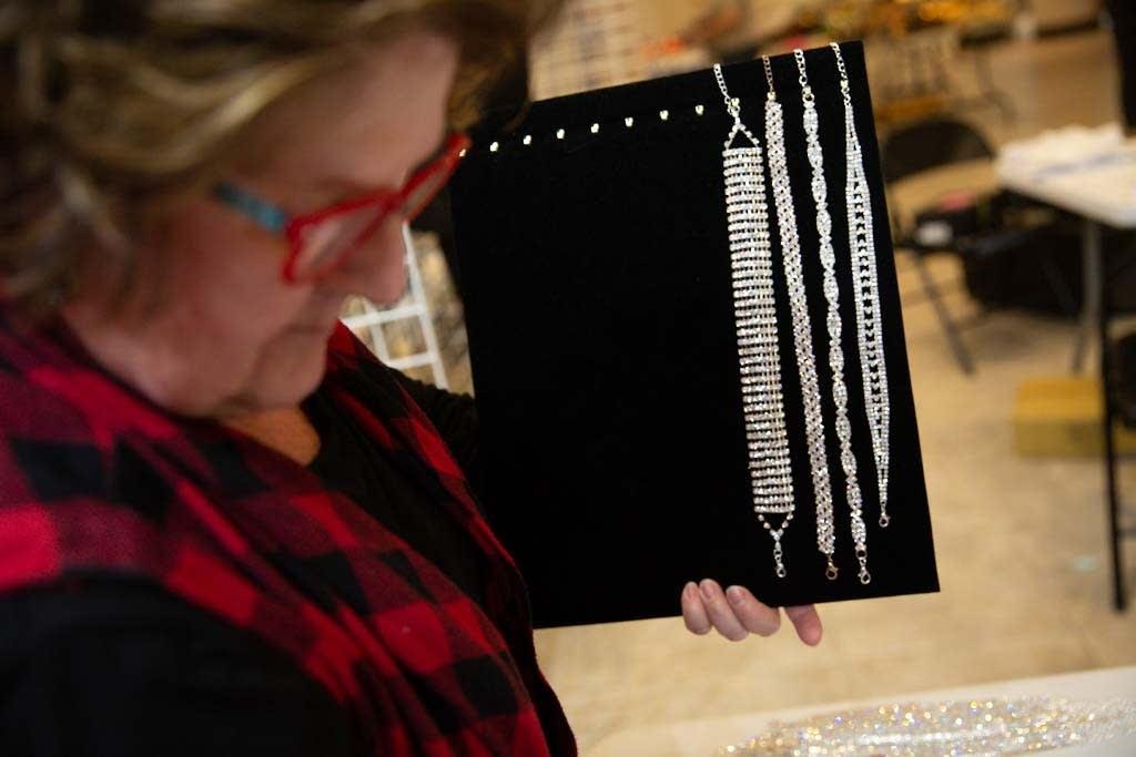 Volunteer Karen Tiedens of Lake Elmo organizes jeweled chokers.