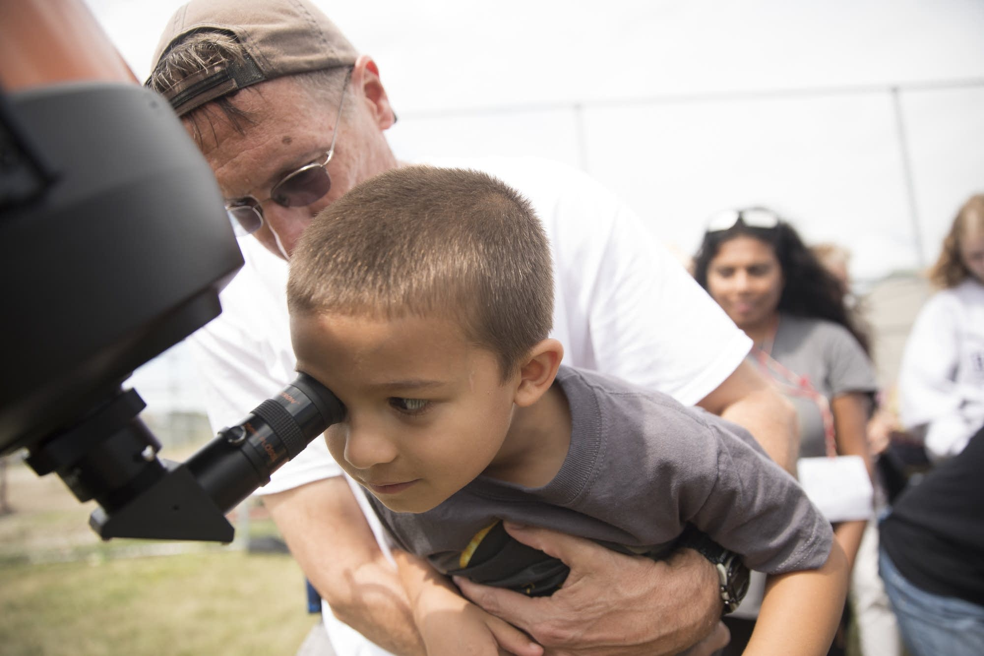 Alek Kokotovich, 5, of Savage, is lifted up to view the solar eclipse.