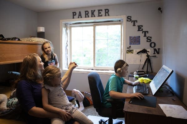 Parker Barnes, 12, right, plays video games while sitting in his room.