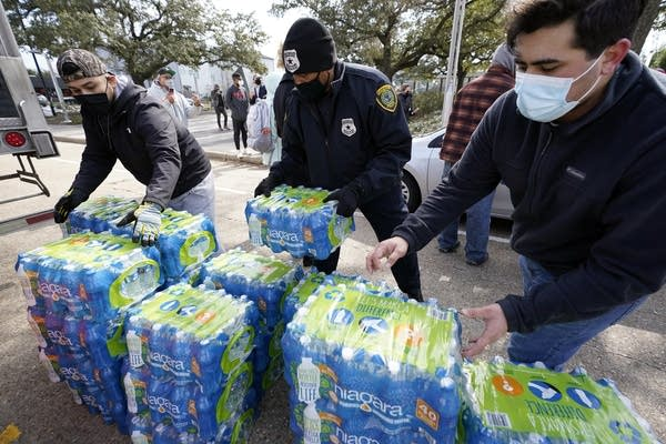 Three people pick up packages of bottled water.