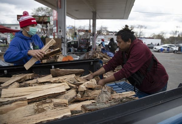 Two people remove wood from the back of a truck.