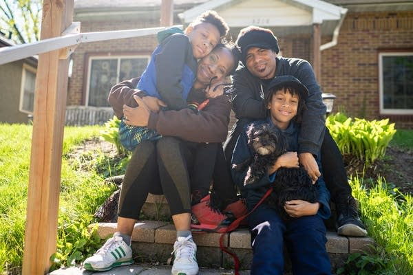 A family sits on the front step of a house.