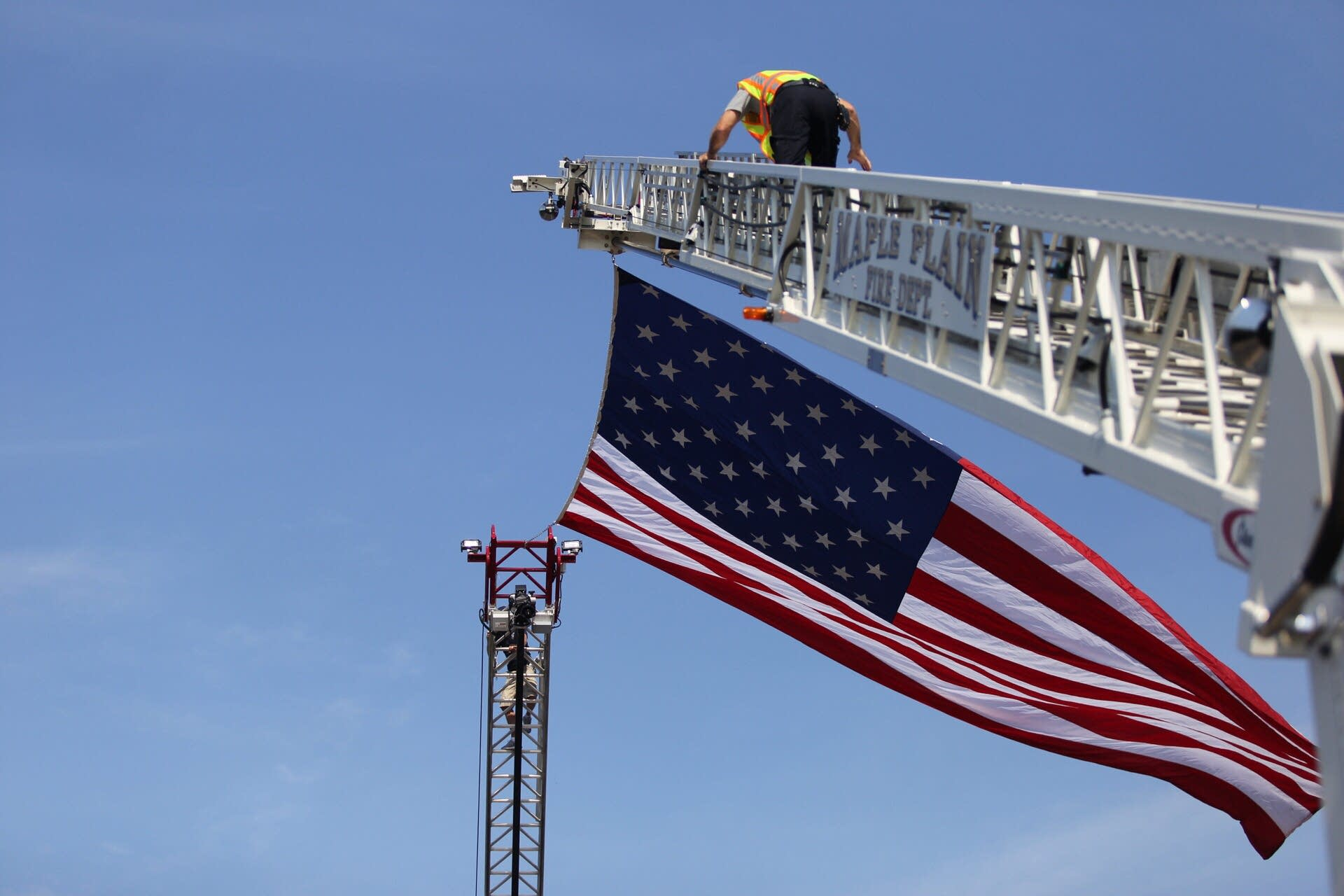 An American flag is hung between fire department trucks.