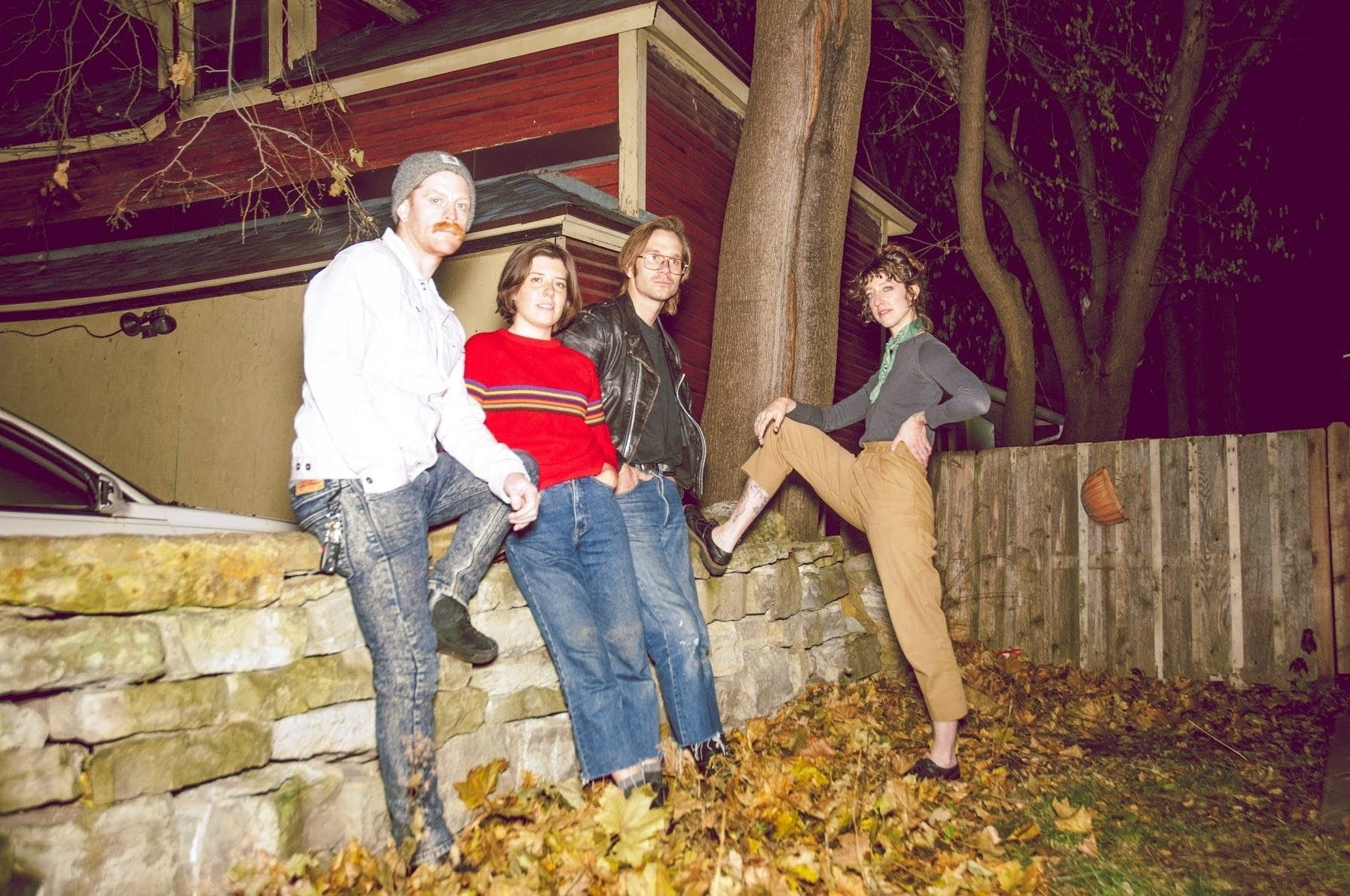 Four people leaning against a wall.