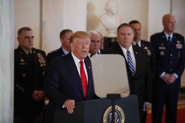 President Trump stands behind a podium with military leaders behind him.