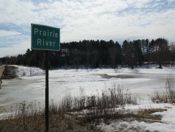 "A sign reading ""Prairie River"" stands next to the ice-covered waterway."
