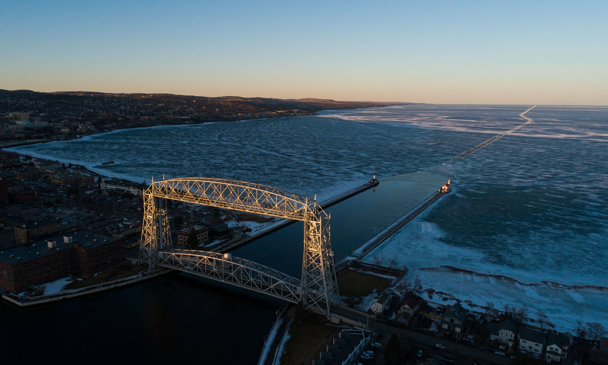 The sun sets on Duluth's aerial lift bridge and the route left in the ice.