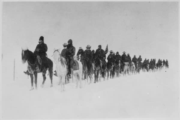 Soldiers on horseback after the massacre.