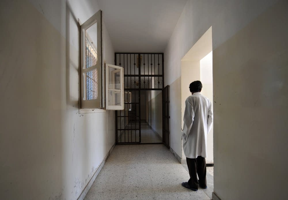 A metal-barred doors stands open in a hall of the