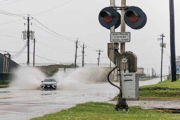 A car drives through a flooded road.