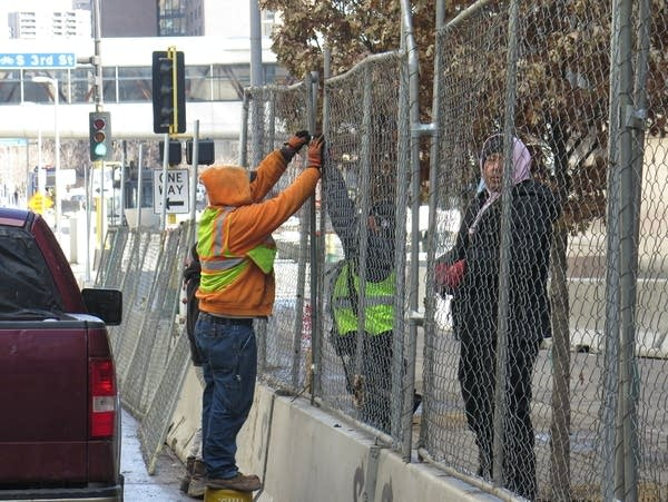 Two people hold up fencing while installing them into concrete.