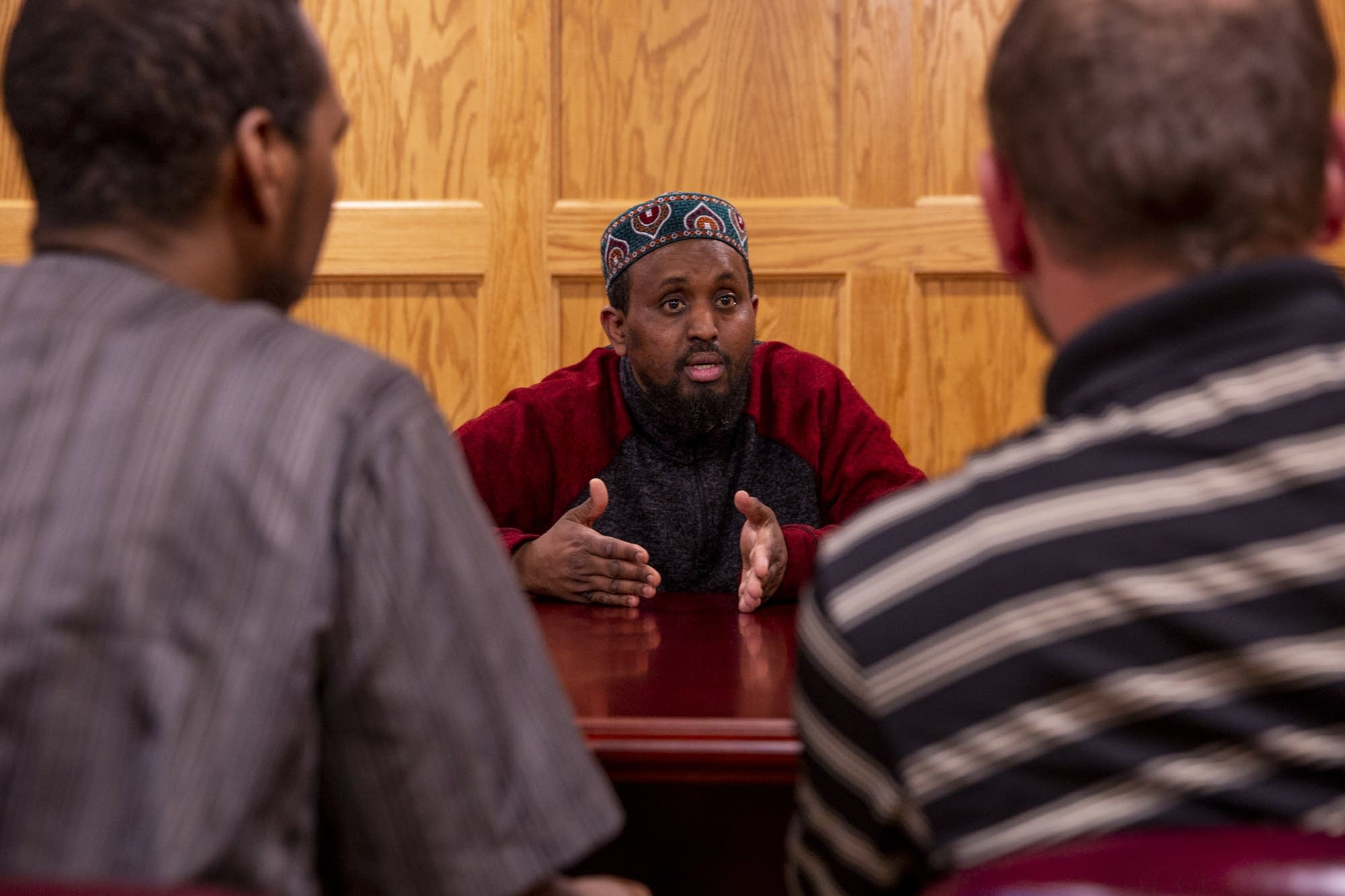 Imam Mohamed Omar speaks to Abdulahi Farah and Zavier Bicott.