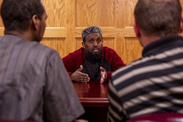Imam Mohamed Omar speaks to Abdulahi Farah and Zavier Bicott.
