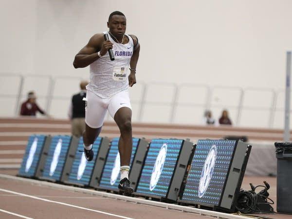 A man runs down an indoor track holding a relay baton.