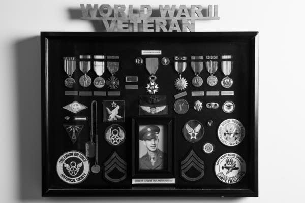 Military Medals hang in a frame.