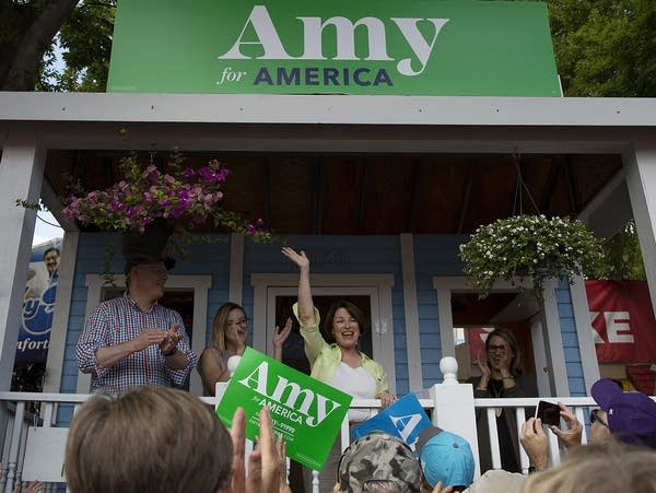A woman waves to a crowd as she stands on a white porch.