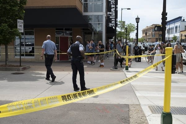 police and crowds following a shooting in Minneapolis
