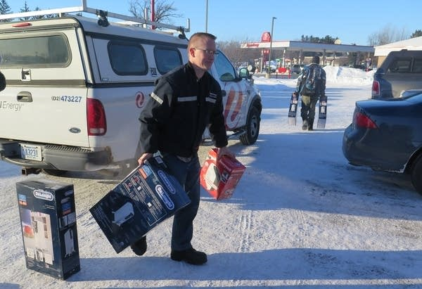 An Xcel Energy employee brings in more space heaters to the AmericInn.