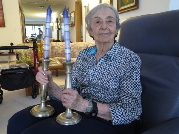 A woman holds two candlesticks.