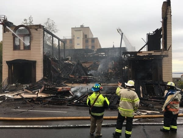 Three firefighters stand in front of a burned building.