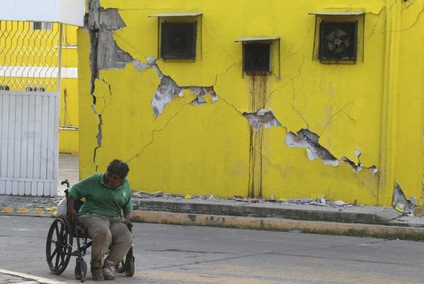 A man sits in his wheelchair amid earthquake damage in Oaxaca state