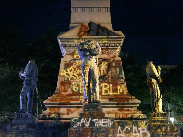 The statues on the Confederate monument are covered in graffiti, beheaded.