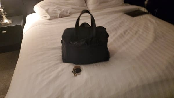 Blurry photo of a handheld travel bag sitting on hotel bed w/ keys