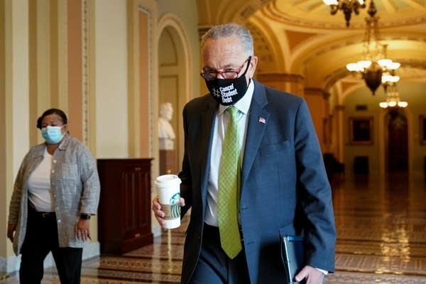 A man in a mask walks through a Capitol hallway.