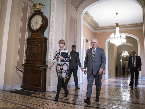 Senate Majority Leader Sen. Mitch McConnell walks down a hall.