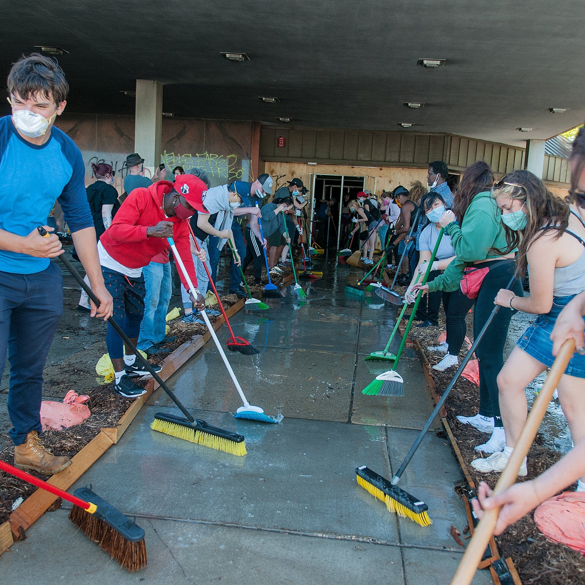 Protestors sweep water out of the partially destroyed Wells Fargo bank