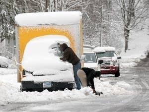 Two men shovel out a moving van Thursday in North Mankato, Minn.