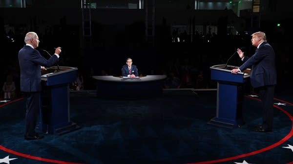 Two men stand behind podiums on opposite ends of the stage.