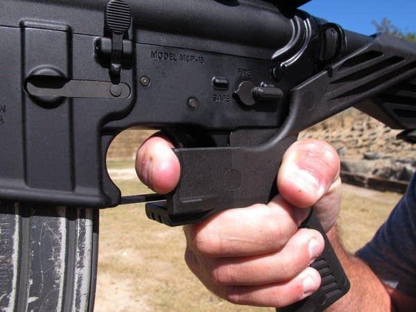 Frankie McRae illustrates the grip on an AR-15 rifle with a 'bump stock.'