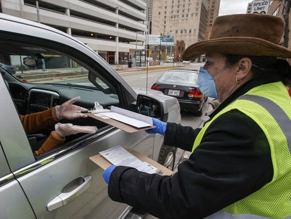 Jill Mickelson helps a drive-up voter