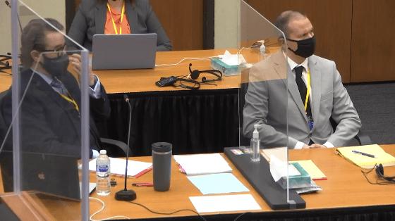 Two men in face masks sit behind a desk.