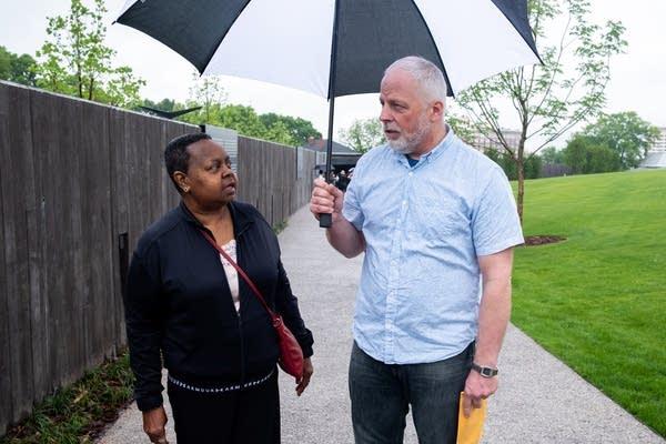 Warren Read and Virginia Huston share an umbrella.