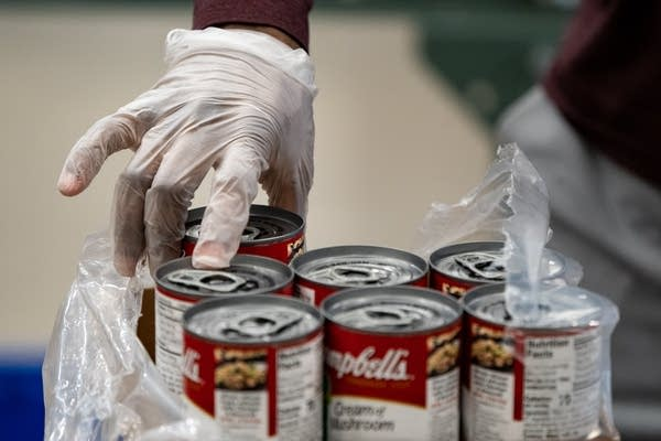 A gloved hand picks up a can of soup.
