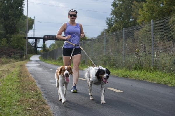 Alicia Kropelnicki runs on the Cedar Lake Trail with her two dogs.