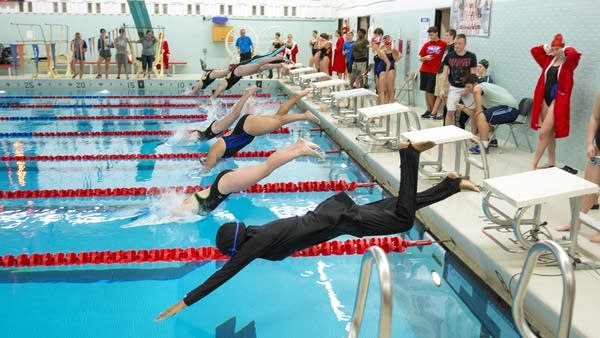 Nimo Gohe, right, dives in for the 50-meter freestyle event.