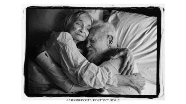 In a black and white photo, an elderly couple embrace laying in bed.