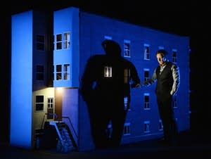 Robert Lepage stands by a model of the building where he grew up.
