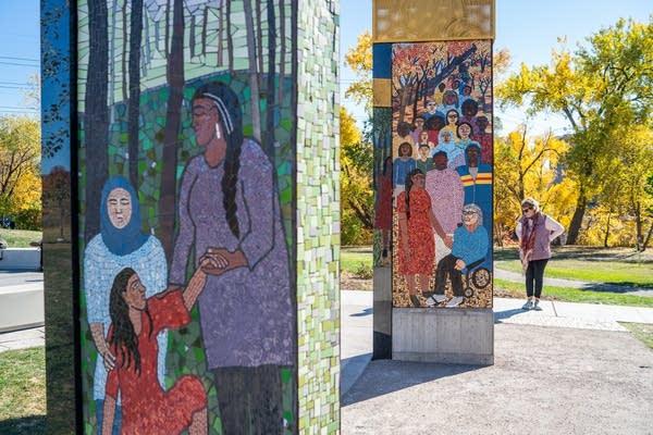 A woman looks at pillars of mosaics.
