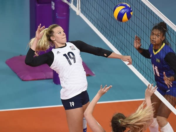 A player jumps to hit a volleyball in the air.