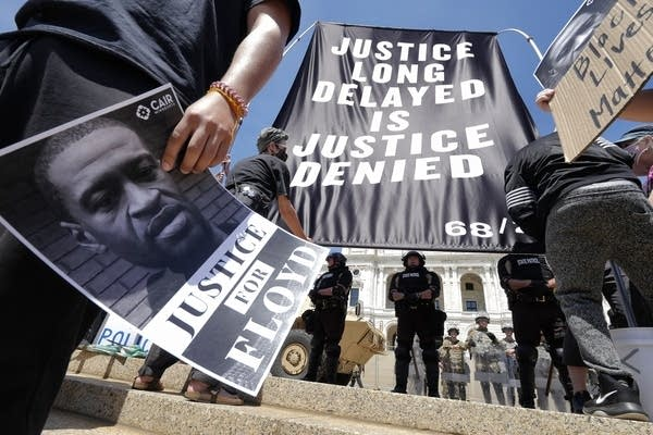 "A sign reads ""Justice long delayed is justice denied."""