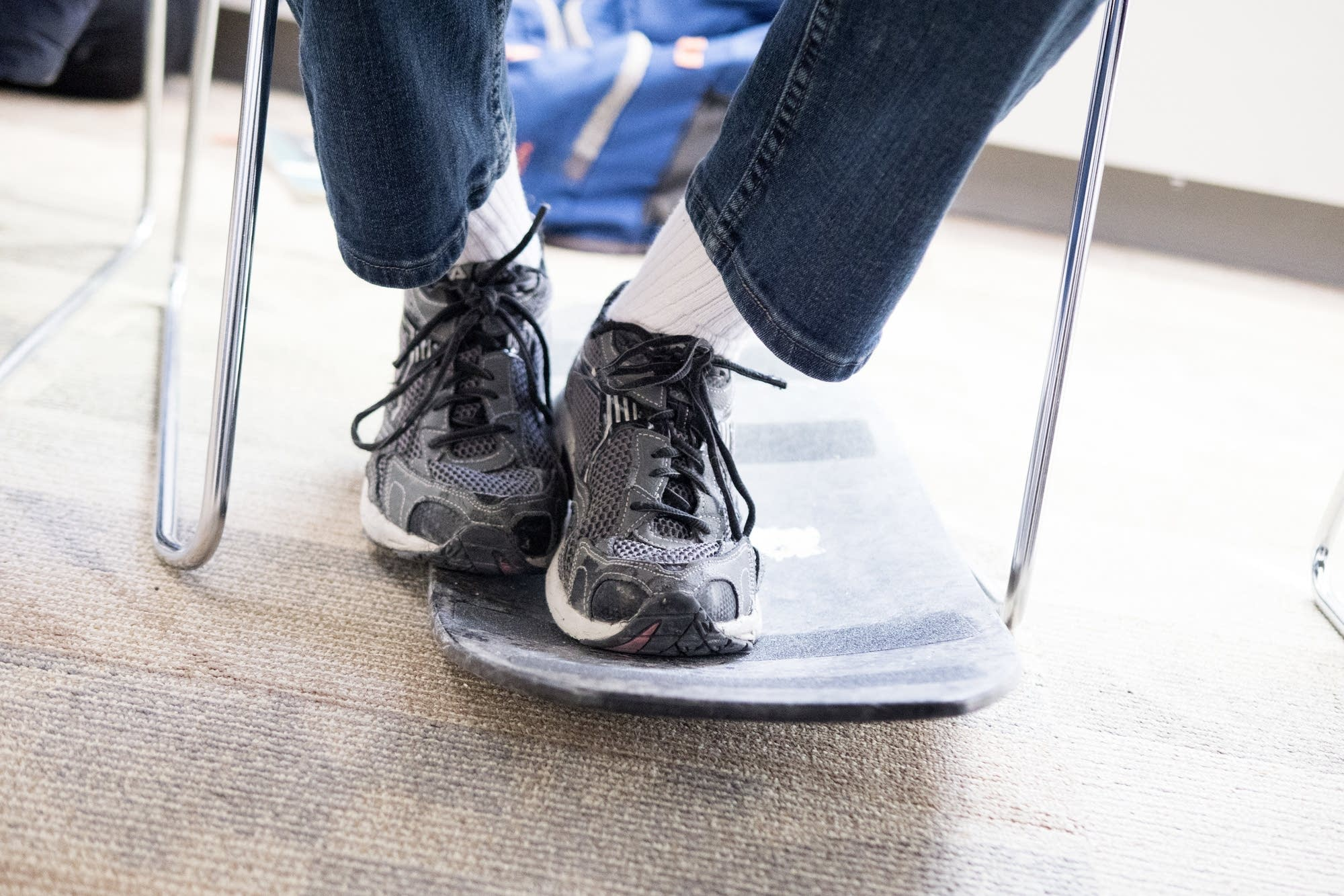 A student rests his feet on a balance board during class at Lionsgate.