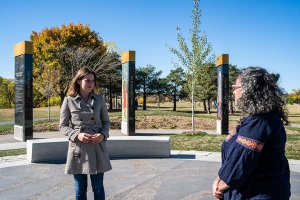 Two women stand in a memorial.